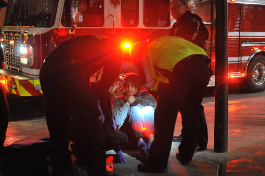 Paramedics attending a scene of an injured person.