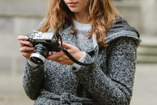 Holding a mirrorless Fuji with a black camera strap