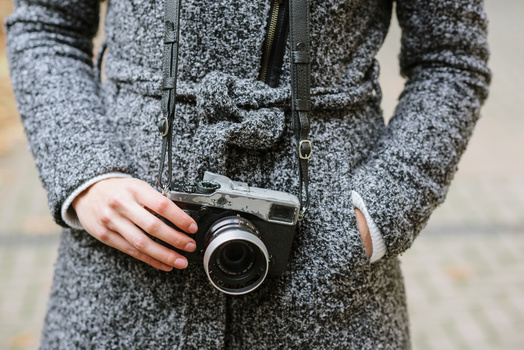 A Fuji mirrorless with a black leather camera strap