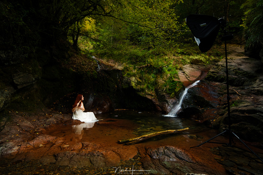 This is strobist photography. A speedlite in a softbox on location, with a model in a small pool next to a waterfall. It is like a studio on location.