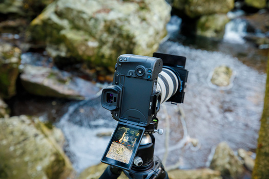 You cannot look through the viewfinder of a mirrorless camera without switching on the camera.