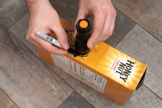 A cereal box is being marked with a permanent marker, prior to cutting