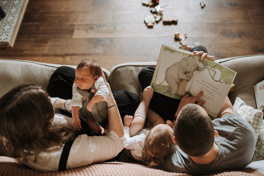 A young family reading a book together on the sofa.