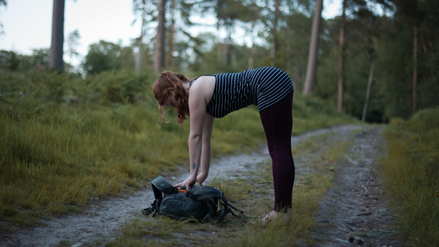 Extend your spine with a forward bend and a camera bag