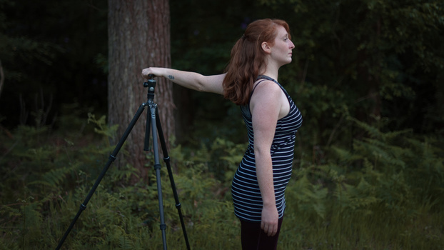 Kat Bayly doing a photography stretch with a tripod