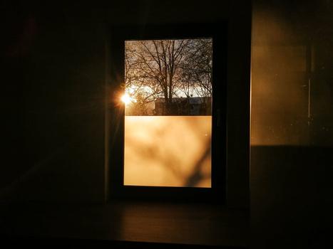 A sun rise coming through the window