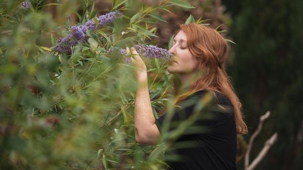 Woman smelling buddleia flower