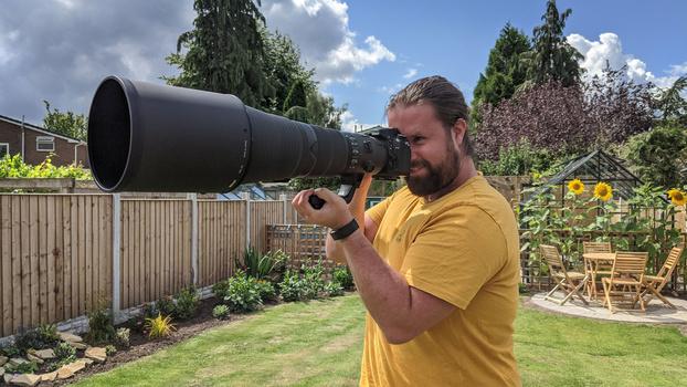 Man holding 600mm lens in garden