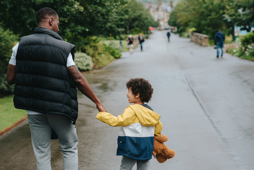 A father walking in the park with his young son.