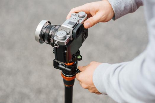 A man using camera on a tripod.