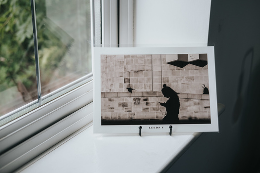 A printed photograph in a black display on a windowsill.
