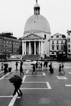People walking by on a street in Venice.