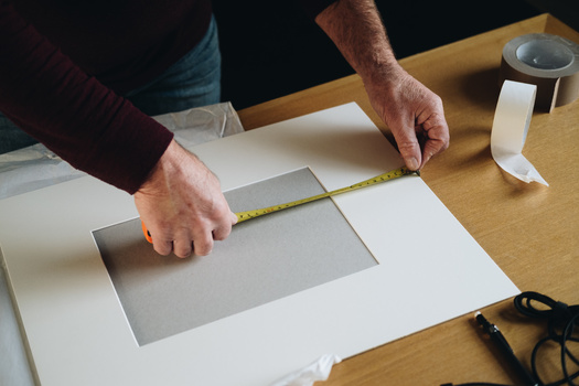A man measuring a photo mount.