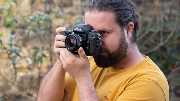 Man with film camera to eye