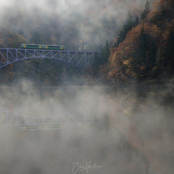 Train running in the river fog by Sho Hoshino
