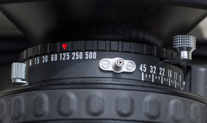 Use the knob on the left to adjust the aperture (the needle barely visible on the right). The black ring with the red arrow is used to select shutter speed. And the right knob cocks the shutter when pulled all the way down.
