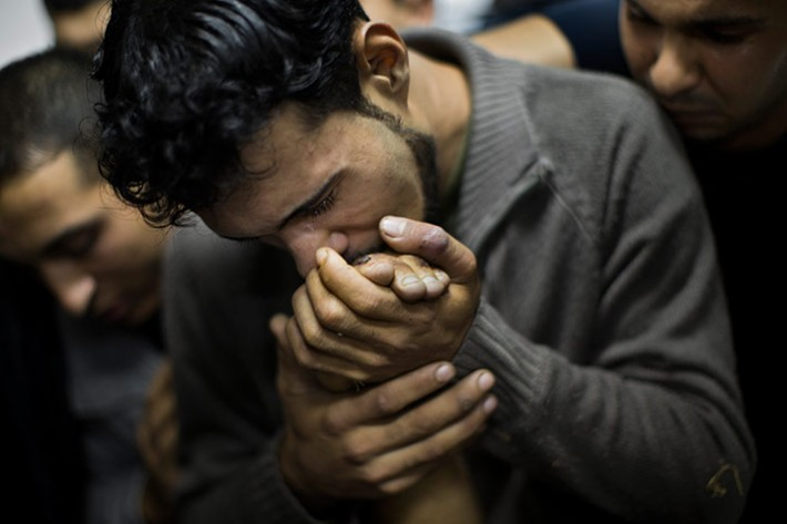A Palestinian man kisses the hand of a dead relative in Shifa Hospital